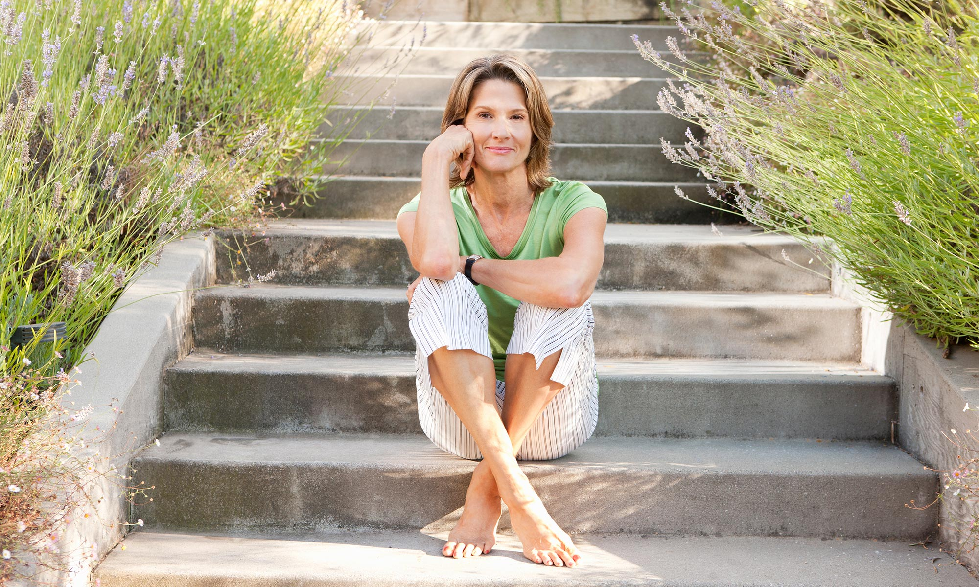 Woman sitting barefoot on steps.